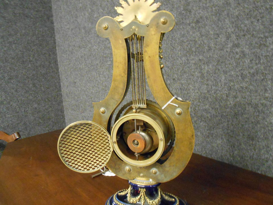 A Louis XVI style gilt bronze mounted lyre form mantel clock