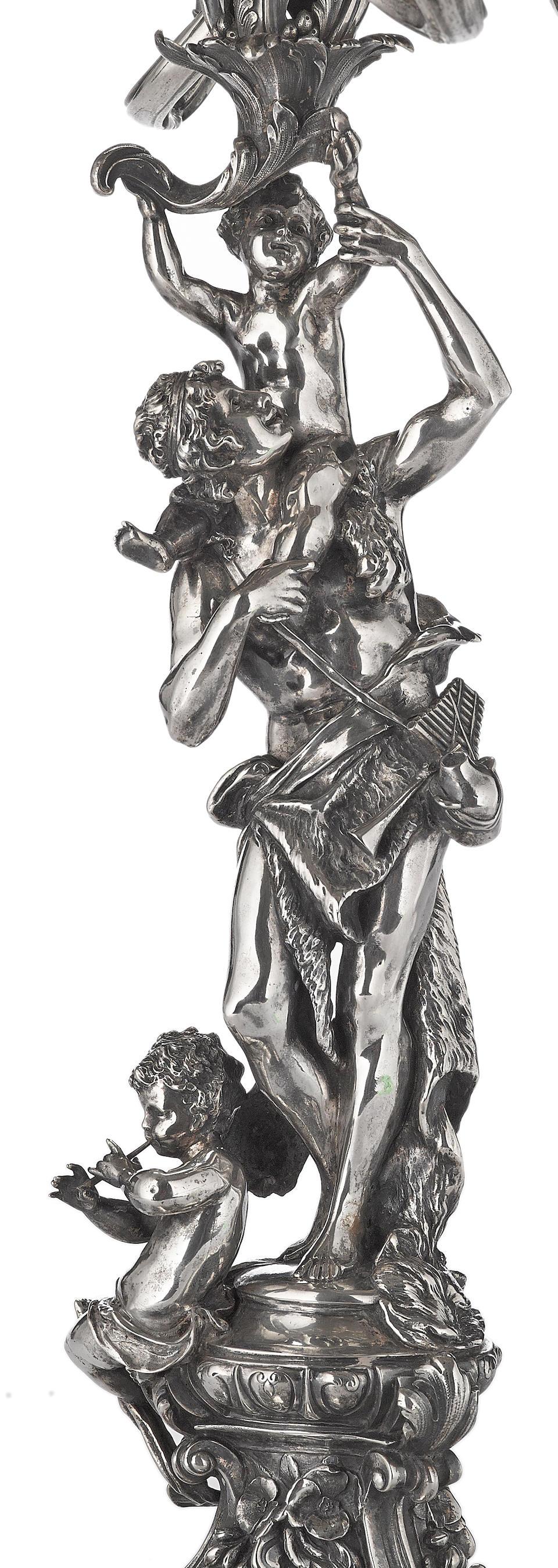 A monumental pair of German  800 standard silver Rococo style figural nine-light candelabra by Körner and Proll; retailed by Gebrüder Friedlander, Berlin,  late 19th century
