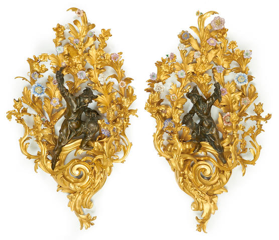 An impressive pair of Rococo style porcelain mounted gilt and patinated bronze four light bras de lumière
