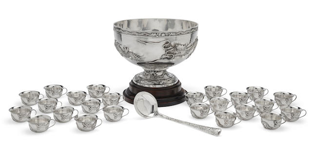 A large silver punch bowl with ladle and twenty four cups Late 19th century