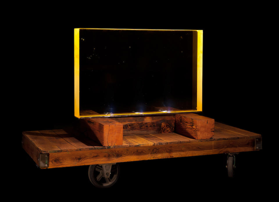 MANHATTAN PROJECT VIEWING WINDOW. An approximately 54 x 36 inch rectangle of heavily leaded glass, 6 inches thick, approximately 1500 lbs, on custom antique wooden cart, glass illuminated from below with 3 custom LED lights.