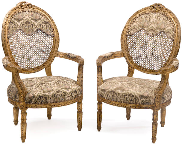 A pair of Louis XVI style giltwood and caned fauteuilsfirst quarter 20th century