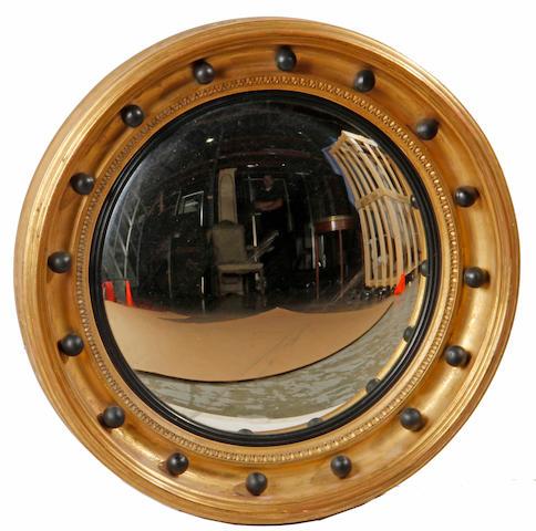 A Regency gilt and ebonized convex mirror