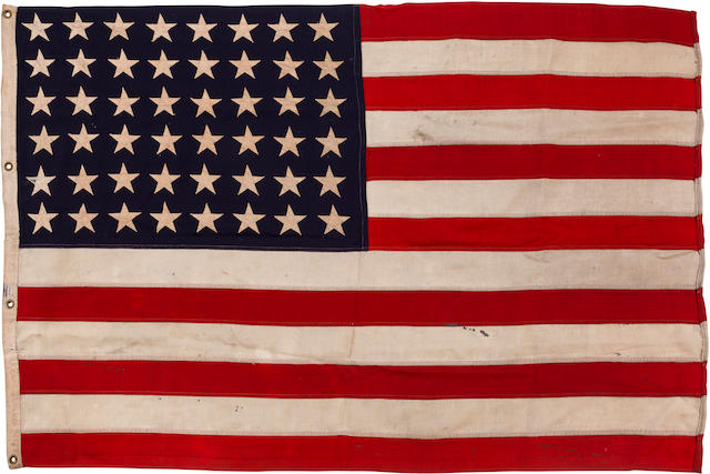 """A 48-Star Ensign flown both on the Salerno Invasion of Sicily, and on D-day On the Normandy beaches  from USS LST-2 """"Dirty Duece,"""" salerno, September 9, 1943 and D-day June 6, 1944 Flag: 61 x 39in (155 x 99cm); photos: 8 x 10in (20 x 25cm)"""