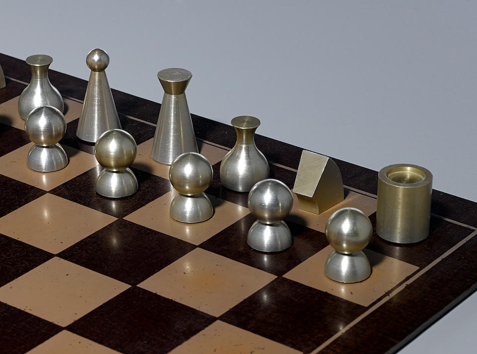 Man Ray Chess Setdesigned circa 1945, this example executed 1947, comprising 32 chess pieces, and chess board, anodized aluminum, Bakelite board, chess board engraved 'Man Ray 1947'heights 1 3/8in (3.4cm) to 2in (5.1cm); chess board 18in x 18in (45.7cm) x (45.7cm)
