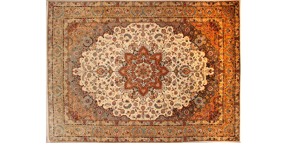 A Tabriz carpet size approximately 9ft. 10in. x 13ft. 6in.