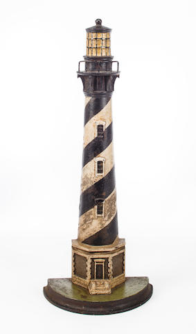 A cast iron doorstop in the form of a lighthouse 22-1/2 x 8-3/4 in. (57.1 x 22.2 cm.), height x width at base.