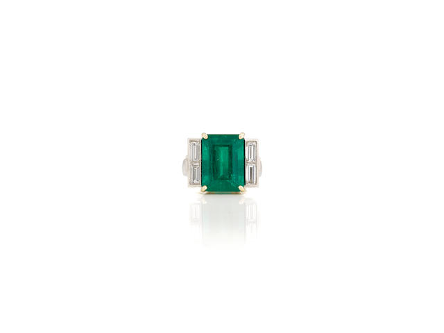 An emerald, diamond, platinum and gold ring