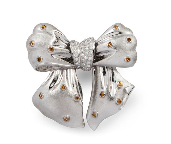 A colored diamond, diamond and 18k white gold  bow brooch