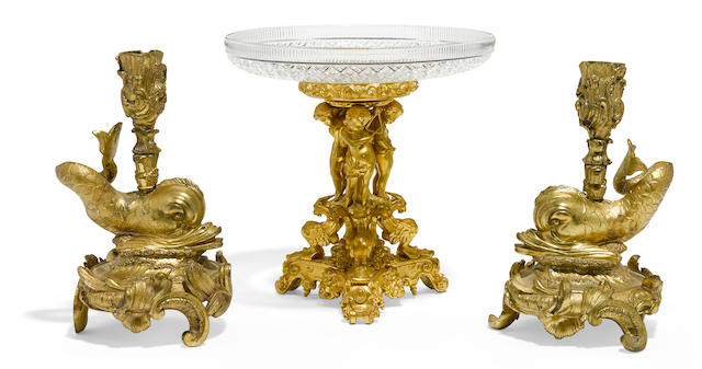 A pair of French gilt bronze dolphin form candlesticks and a gilt bronze and glass compote 19th century