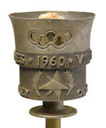 A 1960 Olympic torch. Aluminum, 48.5 cm, top half of crown with pierced Olympic rings above central band with embossed inscription