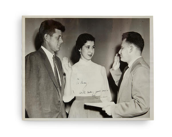"""KENNEDY, JOHN FITZGERALD. Photograph Signed (""""John F. Kennedy"""") and Inscribed, 8 x 10 inch gelatin silver print, of Senator Kennedy and Miss Barelli, at the swearing of the secretarial oath for Miss Barelli,"""