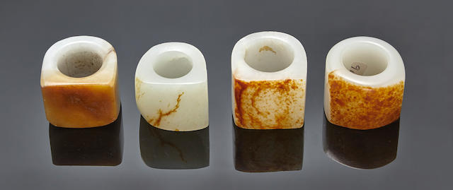 A group of four russet and white jade archer's rings Qing dynasty