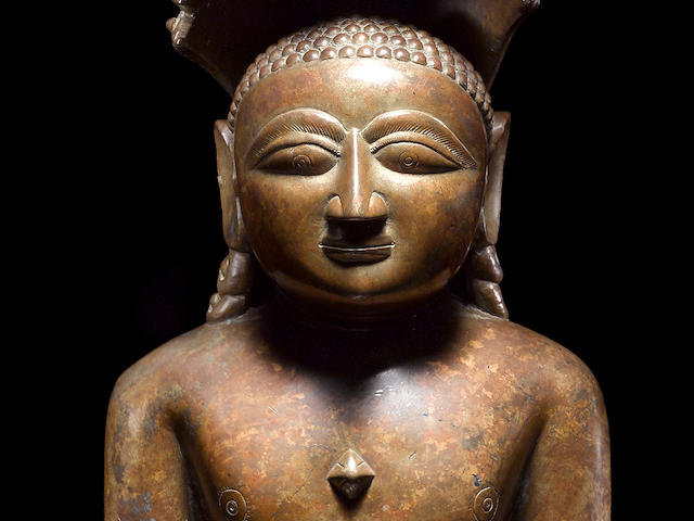 A LARGE IRIDESCENT COPPER ALLOY FIGURE OF PARSHVANATHA CENTRAL OR WESTERN INDIA, CIRCA 15TH CENTURY