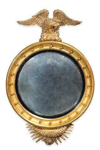 A Regency parcel ebonized carved giltwood convex mirror early 19th century