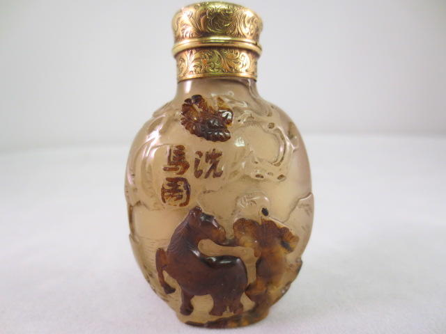 An inscribed chalcedony snuff bottle carved with a figure grooming a horse Suzhou, School of Zhiting, 1750-1830