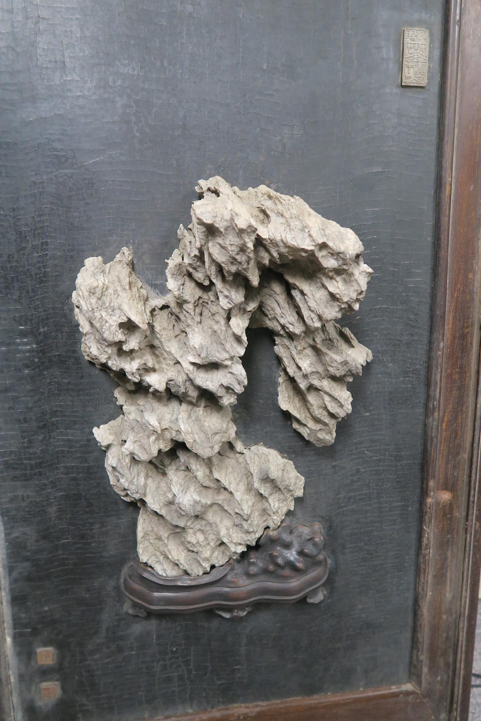 A scholar's rock mounted within a hanging panel