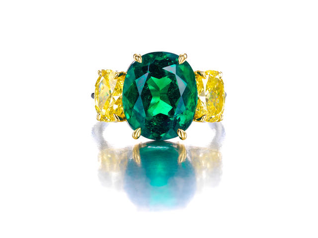 An emerald and Fancy Colored diamond ring