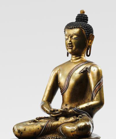 A SILVER AND COPPER INLAID BRASS ALLOY FIGURE OF SHAKYAMUNI BUDDHA TIBET, CIRCA 13TH CENTURY