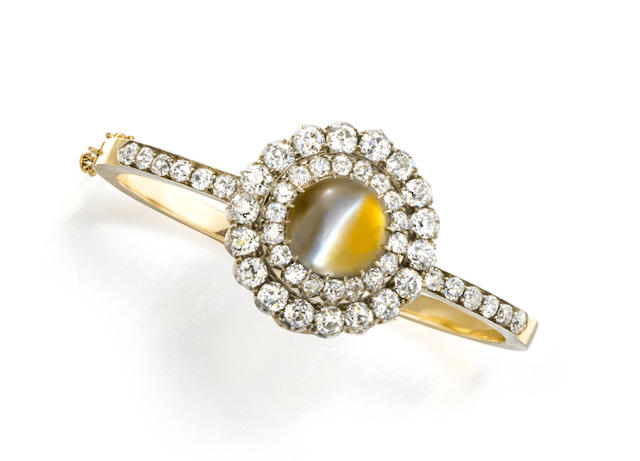 An Antique cat's eye chrysoberyl and diamond bangle/brooch,