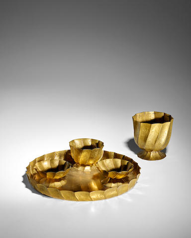 Josef Hoffmann (1870-1956) Smoking Setcirca 1925for the Wiener Werkstätte, comprising tray, three footed cups and footed vase, brass with creased and hand-hammered surface texture, each piece stamped 'WIENER WERKSTÄTTE/MADE IN AUSTRIA/JH'tray height 1 1/2in (3cm); diameter 12 1/4in (31cm); vase height 4 3/4in (12cm); diameter 4 3/4in (12cm); each cup height 2 3/4in (7cm); diameter 4in (10cm)