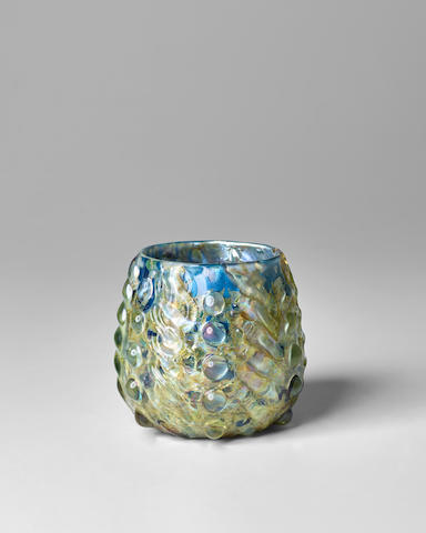 Tiffany Studios (1899-1919) Cypriote Vasecirca 1904textured Favrile glass with vertical relief patterns, with silver and gold foil inclusions, signed 'V617 L.C. Tiffany Favrile'height 3 3/4in (9.5cm); diameter 3 3/4in (9.5cm)