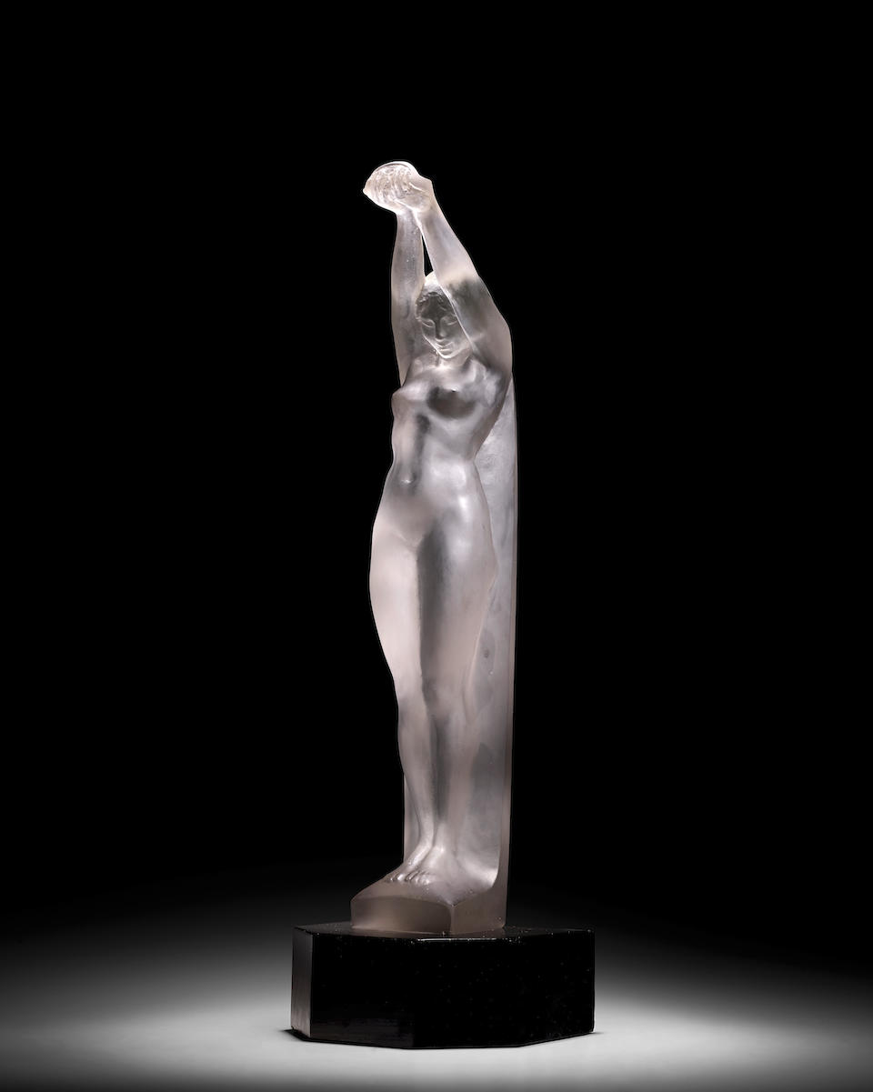 René Lalique (1860-1945) Grande Nue Bras LevésMarcilhac 835, model introduced 1921clear and frosted glass, lacquered wood pedestal,  engraved 'R. LALIQUE FRANCE'height of glass 23 1/4in (59cm); overall height mounted on wood pedestal 24 1/4in (61.5cm); width 5in (13cm); depth 3 1/2in (9cm)