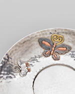 Tiffany & Co. (EST. 1837) Cup and Saucercirca 1880silver with hand-hammered surface, applied with copper and Japanese gold, cup stamped 'TIFFANY & CO./5520M922/STERLING-SILVER/AND OTHER METALS 824' and engraved M.T. de P 1880., saucer stamped 'TIFFANY & CO./4719M922/STERLING-SILVER/AND OTHER METALS 824', engraved M.T. de P 1880, and with French import marks cup height 9in (3.5cm); width 4 1/4in (11cm); saucer  height 3/4in (2cm); diameter 7in (18cm)