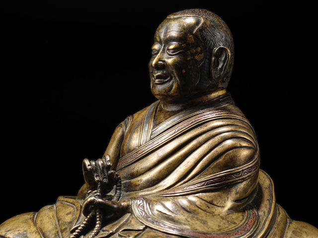 A COPPER AND SILVER INLAID COPPER ALLOY FIGURE OF A BUDDHIST HIERARCH TIBET, 14TH CENTURY
