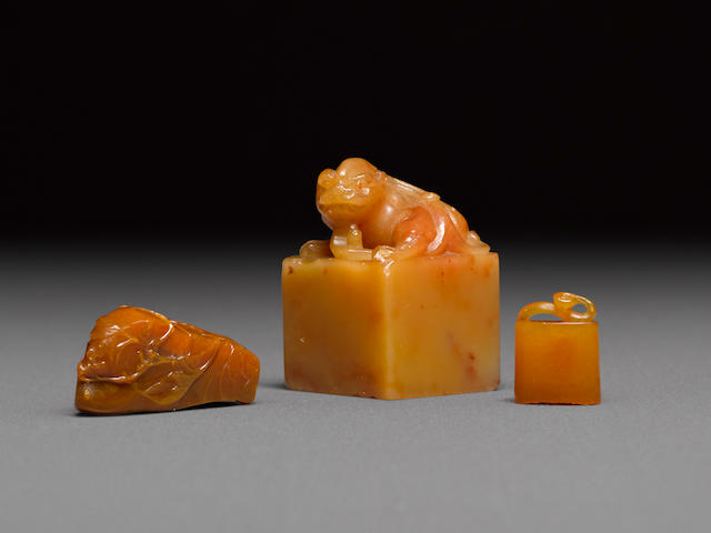 A group of three yellow soapstone seals and carvings (3)