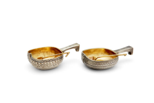A near pair of parcel-gilt salt cellars with spoons first: Sazikov Firm, with Imperial Warrant stamp, St. Petersburg,  1876; second: with Cyrillic mark 'KS', with Imperial Warrant stamp, St. Petersburg, 1871