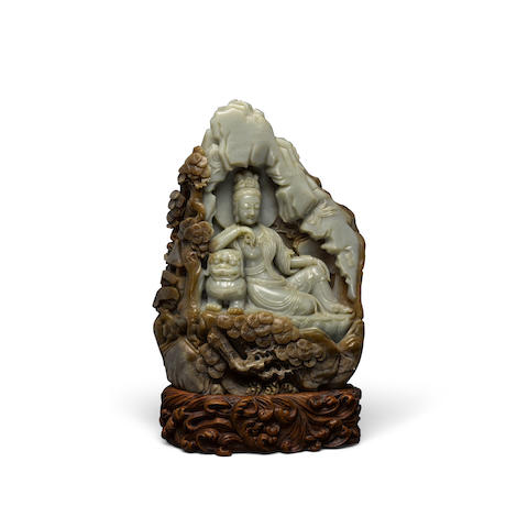 A GREEN AND BROWN JADE GUANYIN GROTTO