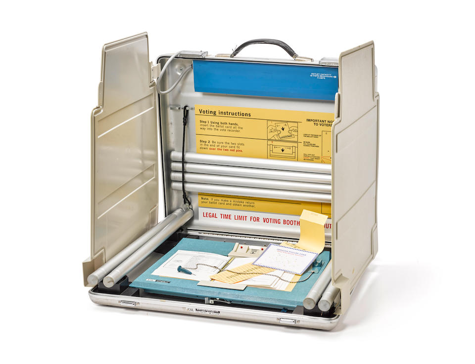 THE HANGING CHAD: FLORIDA, 2000. Florida voting machine, in portable aluminum case with specimen ballots from the 2000 Presidential election,