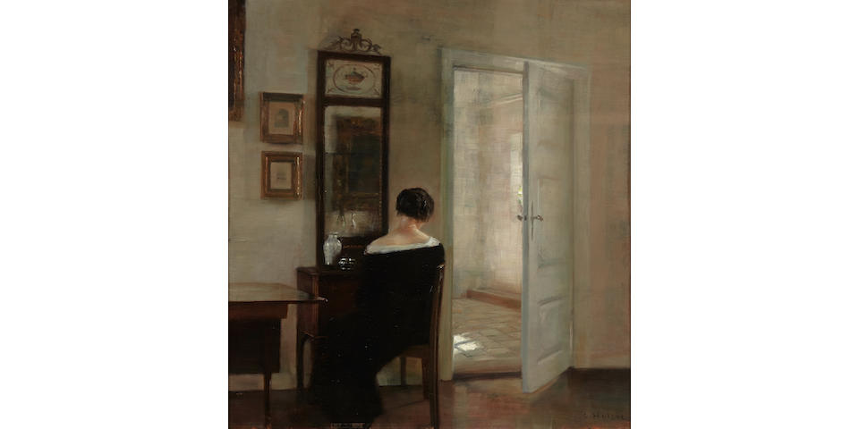 Carl Vilhelm Holsøe (Danish, 1863-1935) A lady seated before a mirror in an interior 22 7/8 x 21 1/4in (58.2 x 54cm)