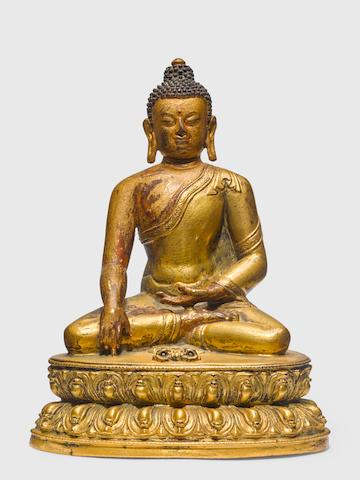 A GILT COPPER ALLOY FIGURE OF SHAKYAMUNI BUDDHA  TIBET, CIRCA 15TH CENTURY
