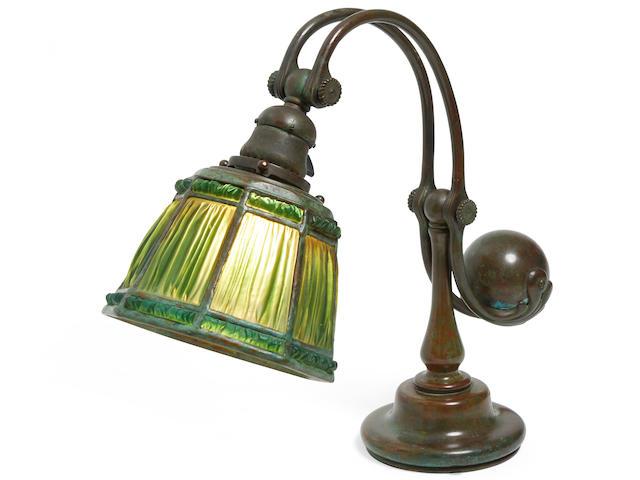 Tiffany Studios (1899-1930) Green Linenfold Counterbalance Desk Lampcirca 1910Favrile glass, patinated bronze, shade stamped 'TIFFANY STUDIOS NEW YORK 1941, underside of base stamped 'TIFFANY STUDIOS NEW YORK 417'height 14 1/2in (37cm); diameter of shade 6in (15cm)