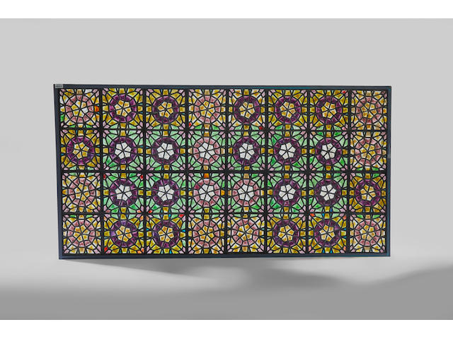 John LaFarge (1835-1910); in the manner of Oversized Islamic Revival Pebble Glass Windowcirca 1890comprising thirty two square glass panels each composed of numerous varicolored rough glass pebbles and arranged in a circular star motif, within a modern steel frameheight 87in (221cm); overall width 46 1/2in (119cm)