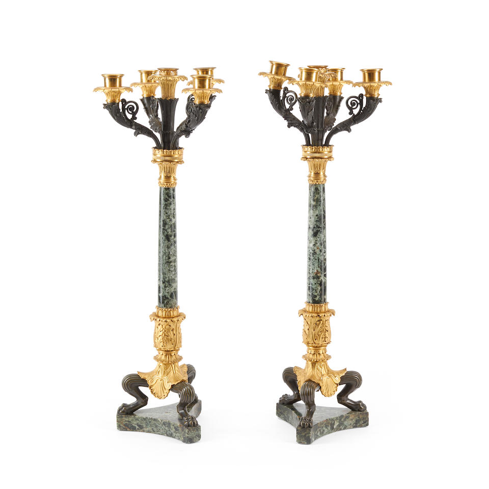 A pair of Charles X style gilt and patinated bronze and marble five-light candelabra