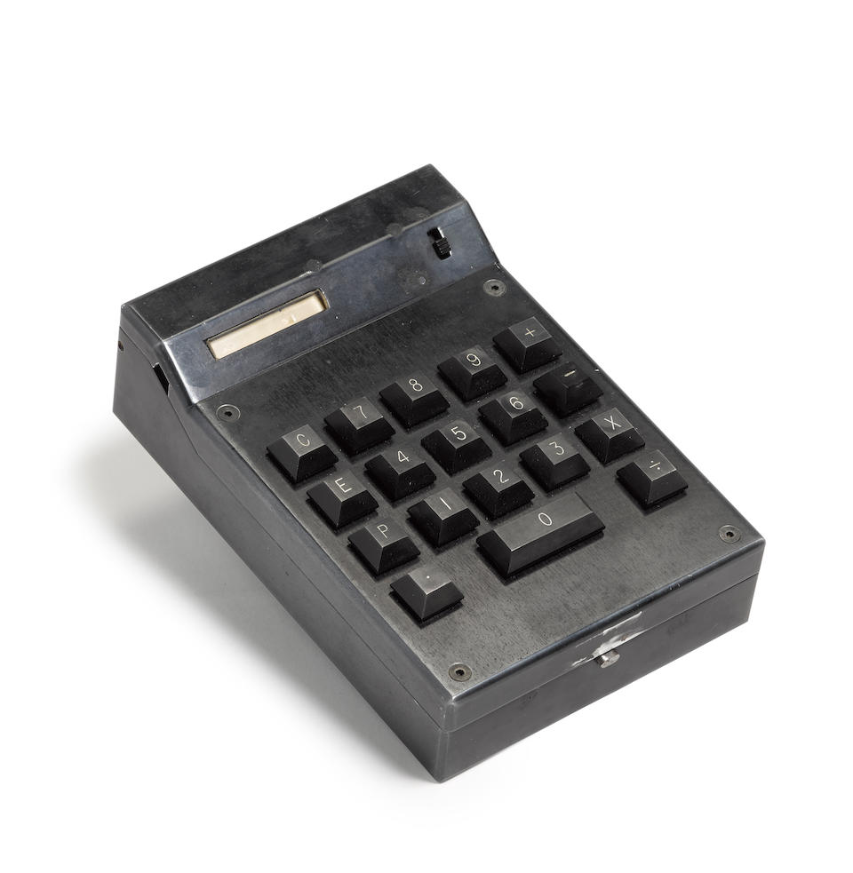 "TEXAS INSTRUMENTS CAL-TECH PROTOTYPE HANDHELD CALCULATOR 1965-1967 Original milled aluminum hinged case finished in black, 155 x 105 x 43 mm, 18-button keypad including zero bar, number readout window, power switch, power charger plug, opens to reveal clear panel cover array of 4 Large-Scale Integration silicon ""slices"" and 3 shift register chips on a circuit board, thermal printer with thin paper roll, black plexiglass panel covering potted battery group and discretionary circuitry for power supply,"
