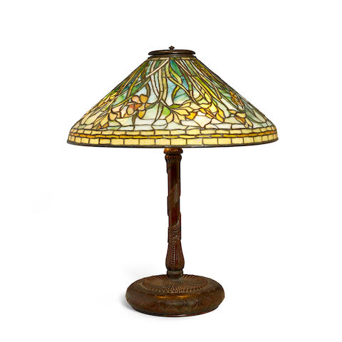 Tiffany Studios (1899-1930) Daffodil Table Lampcirca 1905leaded glass, patinated bronze, shade with bronze tag stamped 'TIFFANY STUDIOS NEW YORK', base stamped '28619 TIFFANY STUDIOS NEW YORK' with maker's monogramheight 25 1/2in (64.7cm); diameter of shade 20 1/4in (51.4cm)