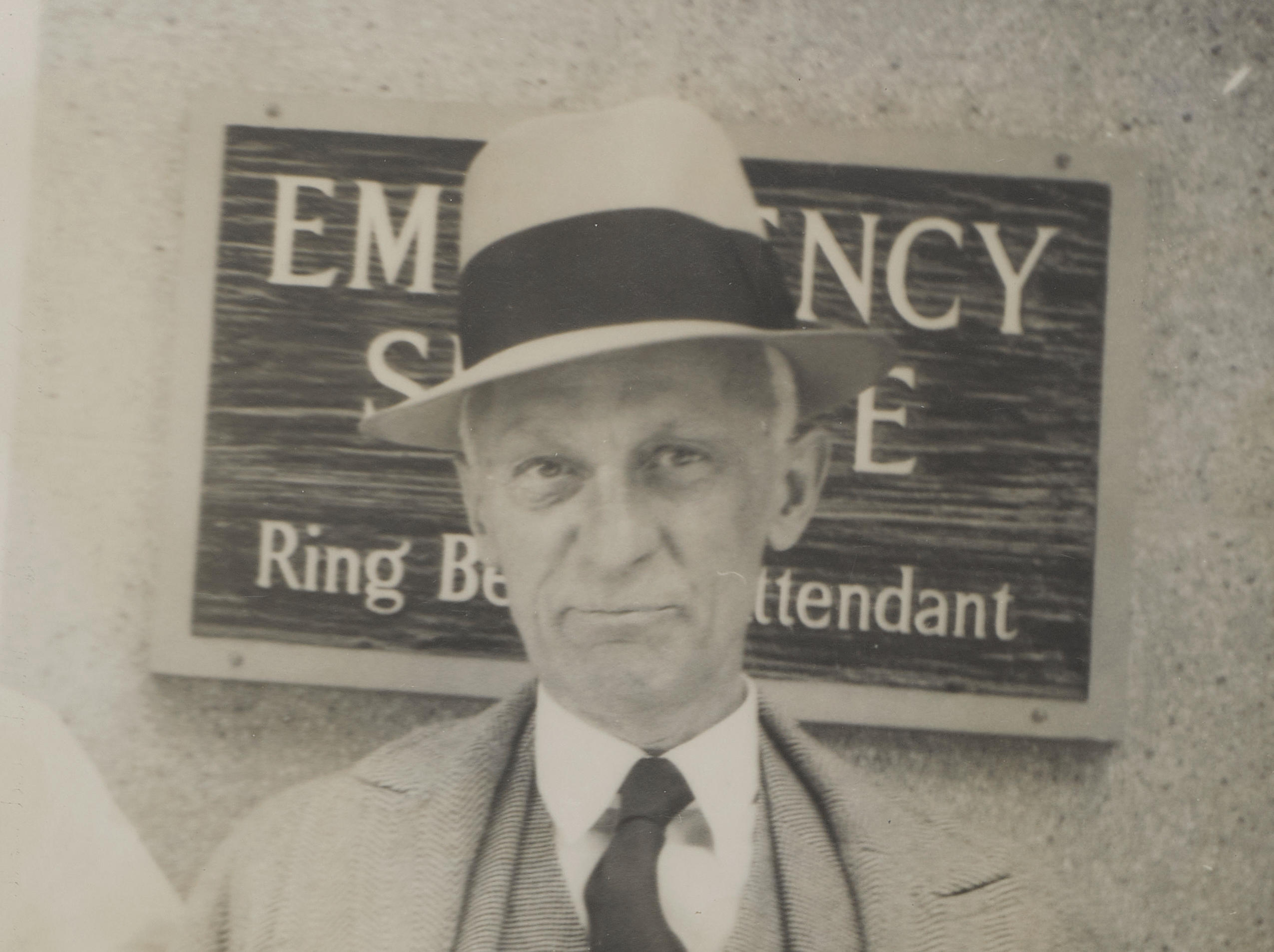"""""""UNMISTAKBLY AN EMERGENCY."""" CUSHING, HARVEY. 1869-1939. Original Photograph annotated by Harvey Cushing, a 5 x 8 inch gelatin silver print depicting Cushing at the emergency entrance to New Haven Hospital, annotated in Cushing's hand """"unmistakably an emergency,"""" c. 1937"""