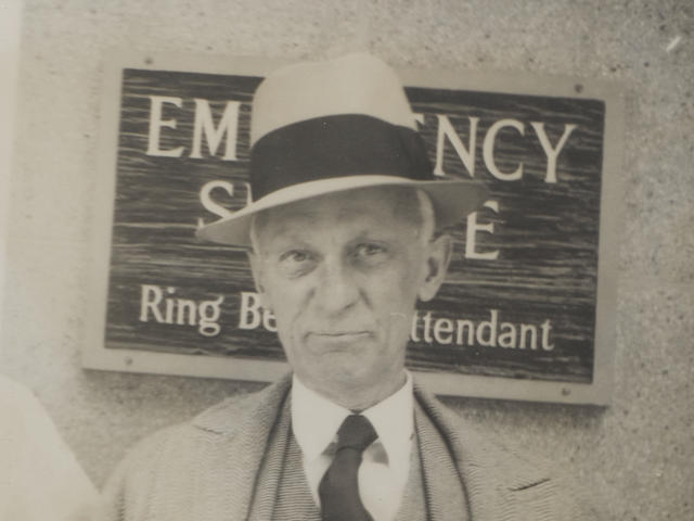 """UNMISTAKBLY AN EMERGENCY."" CUSHING, HARVEY. 1869-1939. Original Photograph annotated by Harvey Cushing, a 5 x 8 inch gelatin silver print depicting Cushing at the emergency entrance to New Haven Hospital, annotated in Cushing's hand ""unmistakably an emergency,"" c. 1937"